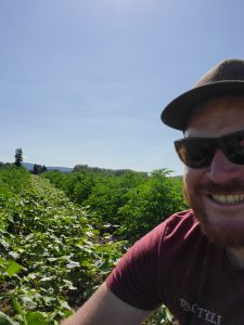 Nick smiling in a selfie in the field